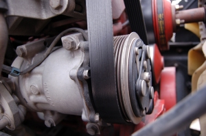 Closer inspection shows the A/C compressor drive belt is riding off track by two teeth, but that's not all. The belt is actually rubbing up against the head of a bolt. As it wears, rubber material is grinding off and building up on top of the bolt.