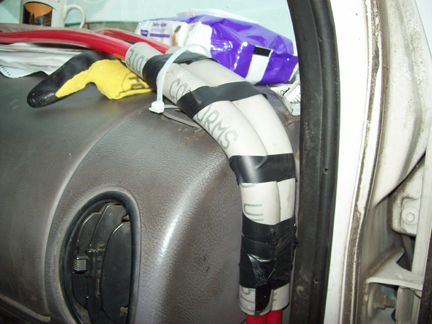Two pieces of plastic electrical conduit help the PEX tubing make that critical bend up onto the dashboard, while also protecting it from damage in the door jamb area. A zip tie attached to the side window vent secures the assembly in place, while electrical tape fastens the supply and return lines together.